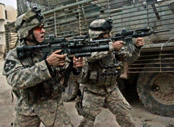 The grenadier is engaging the enemy with his M203 40mm Grenade Launcher supported by the M203 forward handgrip called the M203grip.